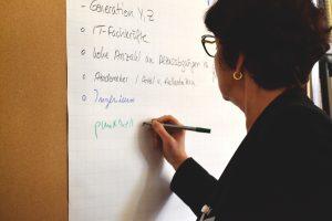 Eine Frau schreibt an einem Flipchart
