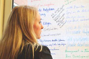 Eine Frau steht vor einem Whiteboard und liest die Notizen