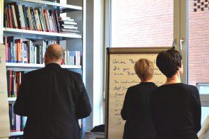 Zwei Frauen und ein Mann stehen vor einem Flipchart-Papier, das am Fenster klebt