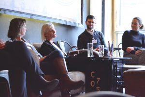 Drei Frauen und ein Mann sitzen zusammen und unterhalten sich