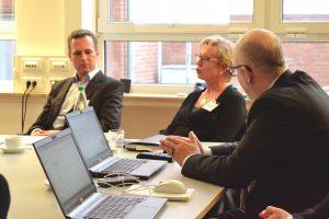 Zwei Männer und eine Frau unterhalten sich bei einer Konferenz