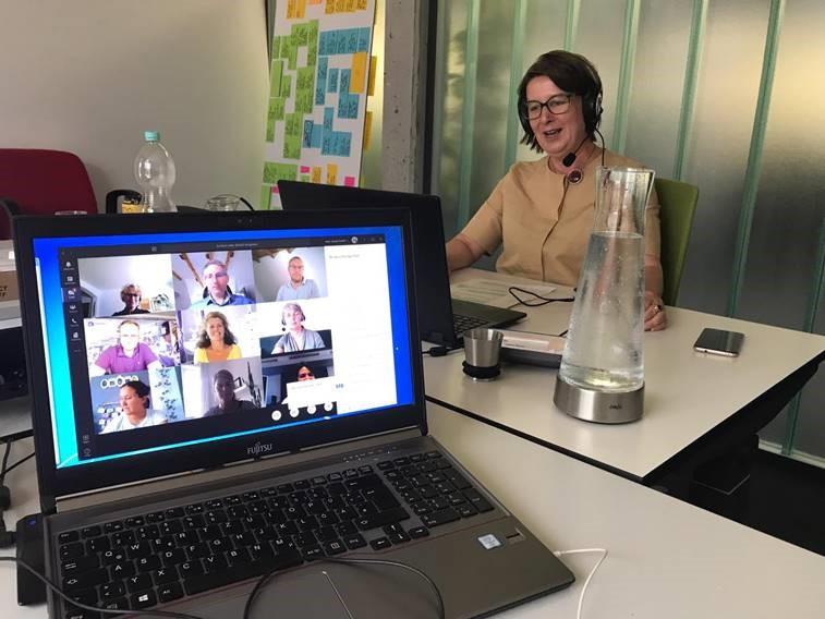 Eine Frau mit Headset sitzt am Schreibtisch in einer Videokonferenz